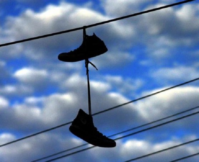 Boots shoes sneakers on wire