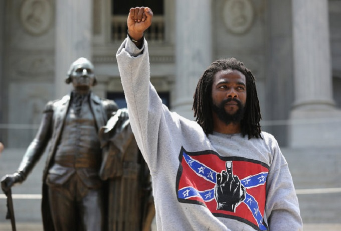 COLUMBIA, SC - JULY 18: A man holds a black power salute during a Black Educators for Justice rally at the South Carolina state house on July 18, 2015 in Columbia, South Carolina. The White Knights of the Ku Klux Klan were scheduled to hold a rally there afterwards, and police presence was heavy to prevent altercations between the two camps. (Photo by John Moore/Getty Images)
